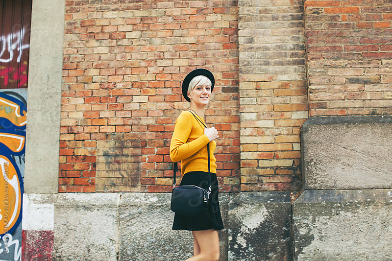 Modern woman walking in front of a brick wall in Barcelona. by BONNINSTUDIO for Stocksy United