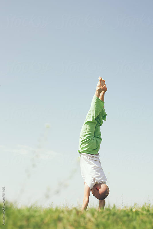 Young Man Doing a Handstand in a Field by Lumina for Stocksy United