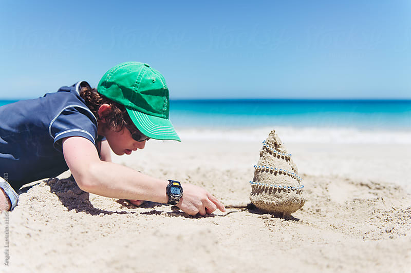 Boy making a very small sand christmas tree at the beach in Australia at Christmas by Angela Lumsden for Stocksy United