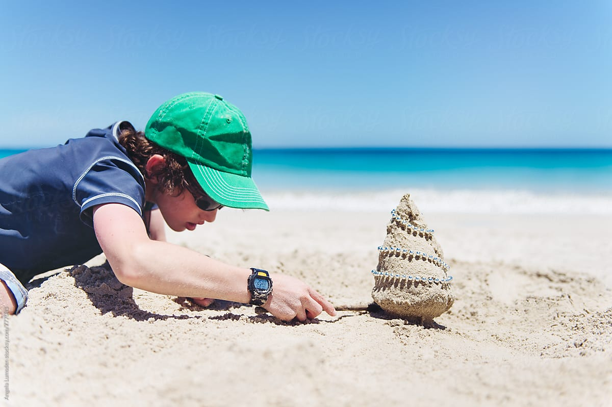 boy making a very small sand christmas tree at the beach in australia at christmas by - Christmas At The Beach