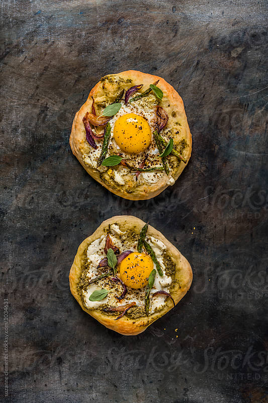 Pesto Egg Onion and Asparagus Pizza by suzanne clements for Stocksy United