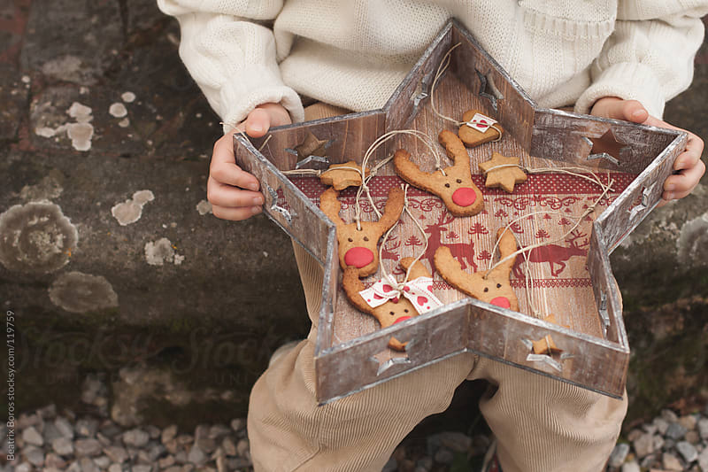 Boy holding Christmas coookies ornaments in a star shape tray. by Beatrix Boros for Stocksy United