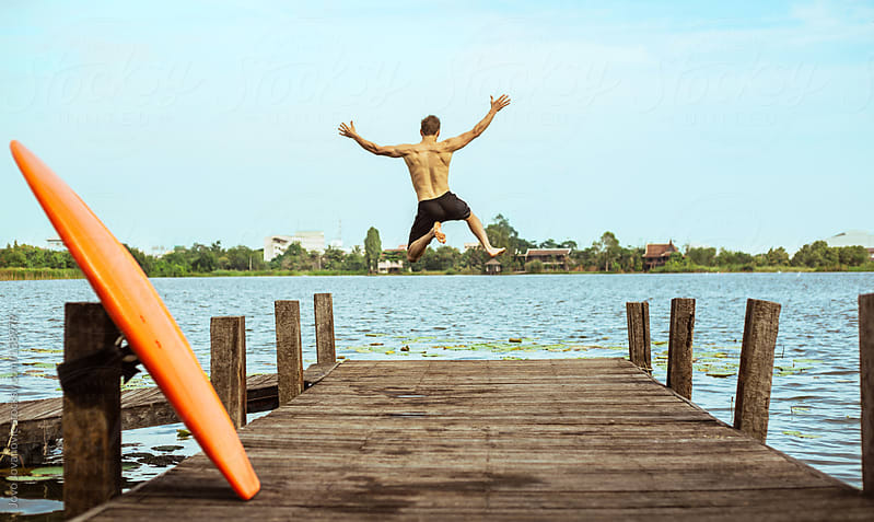 Young man jumping into the lake from a wooden pier.  by Jovo Jovanovic for Stocksy United