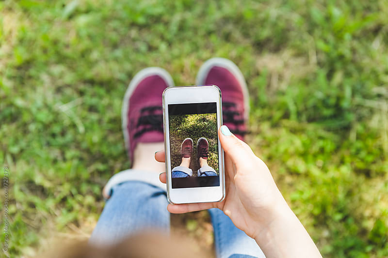 Teen Girl Taking Pictures of Her Shoes with her Mobile Phone at the Park by Giorgio Magini for Stocksy United