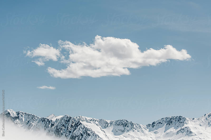 Mountain peaks with snow and cloudy by Jordi Rulló for Stocksy United