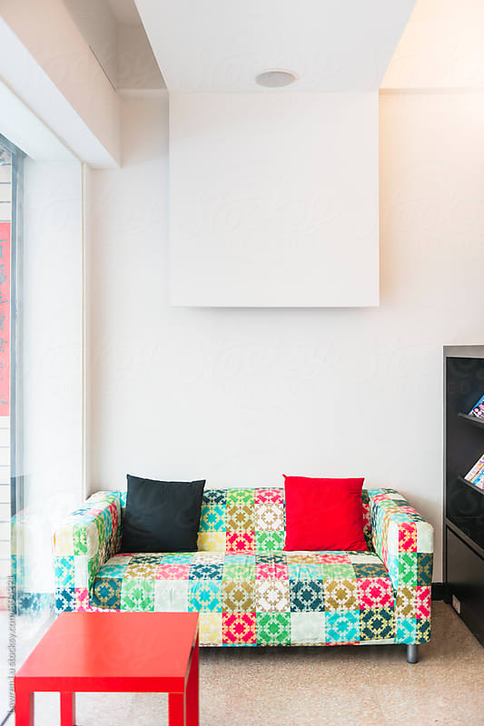 Colorful patchwork sofa with black and red cushions  by Lawren Lu for Stocksy United