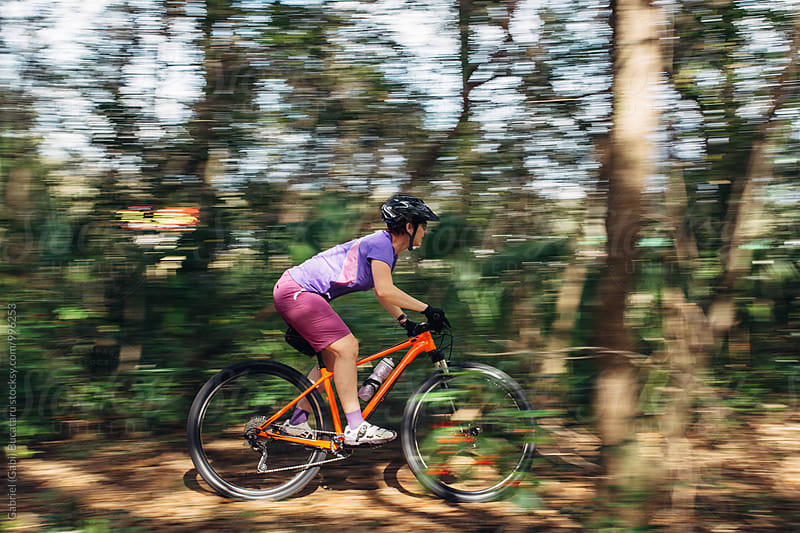 Female mountain bike rider in motion by Gabriel (Gabi) Bucataru for Stocksy United
