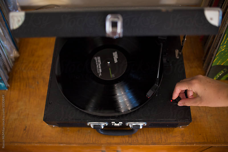 Adjusting the volume of a turntable by Reece McMillan for Stocksy United