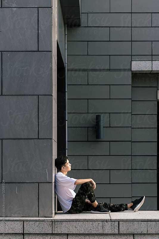 Young Chinese man sitting outside by MaaHoo Studio for Stocksy United