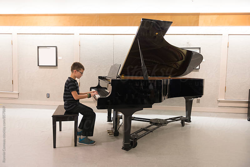 Boy At Piano Recital by Ronnie Comeau for Stocksy United