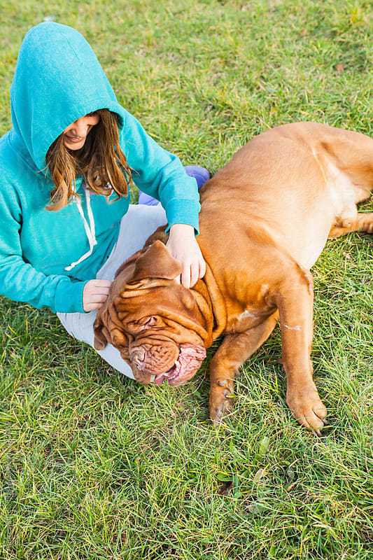 Girl cuddle her dog on grass. by Audrey Shtecinjo for Stocksy United