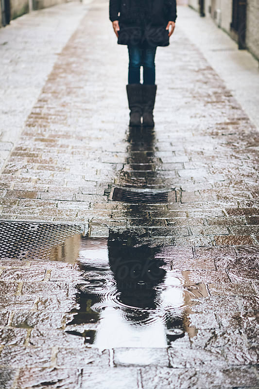 Woman standing against a puddle during a rainy day by GIC for Stocksy United