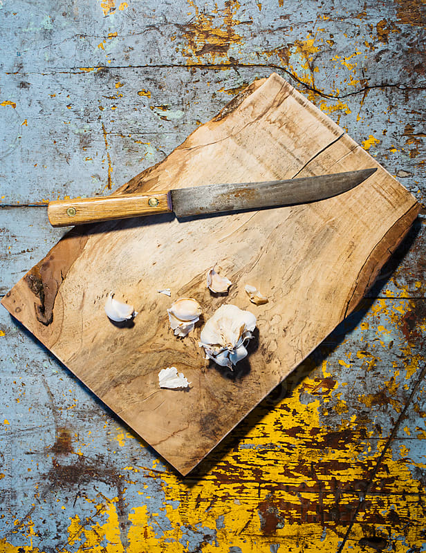 Garlic Being Cut On Wood Cutting Board On Top Of Painted Wood Table by Jack Sorokin for Stocksy United