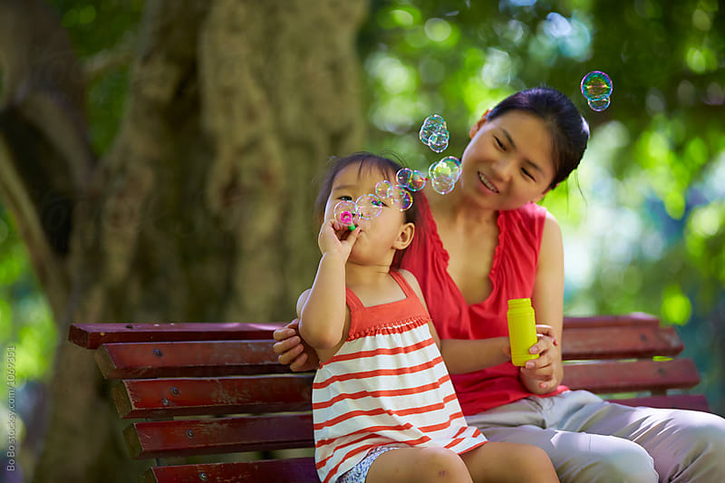 lovely little asian girl blowing soap bubble by Bo Bo for Stocksy United