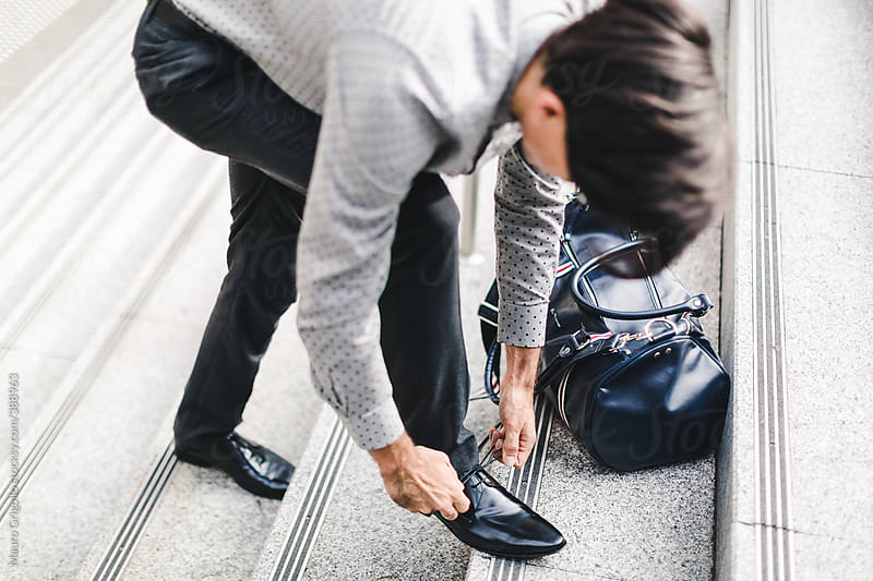 Businessman ties the shoelaces by Mauro Grigollo for Stocksy United