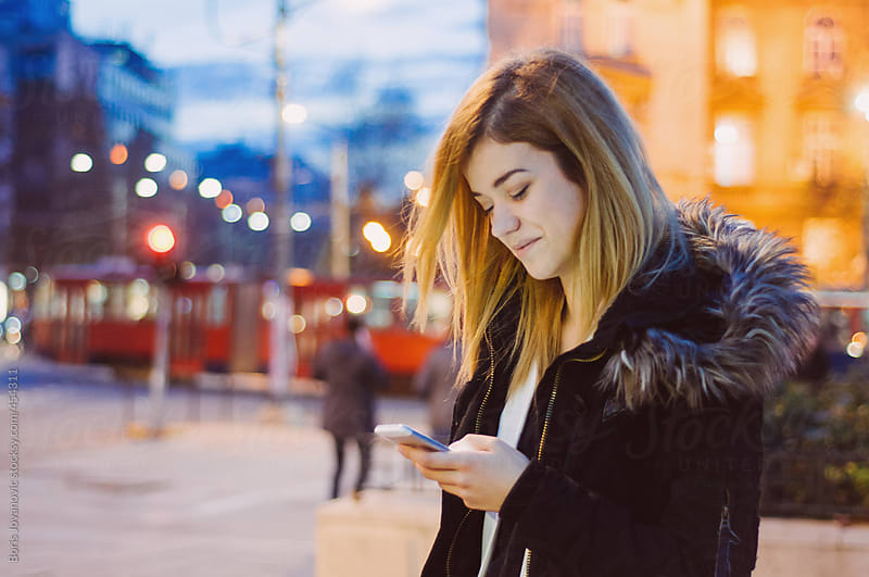 Young blond female using a smartphone on the street by Boris Jovanovic for Stocksy United