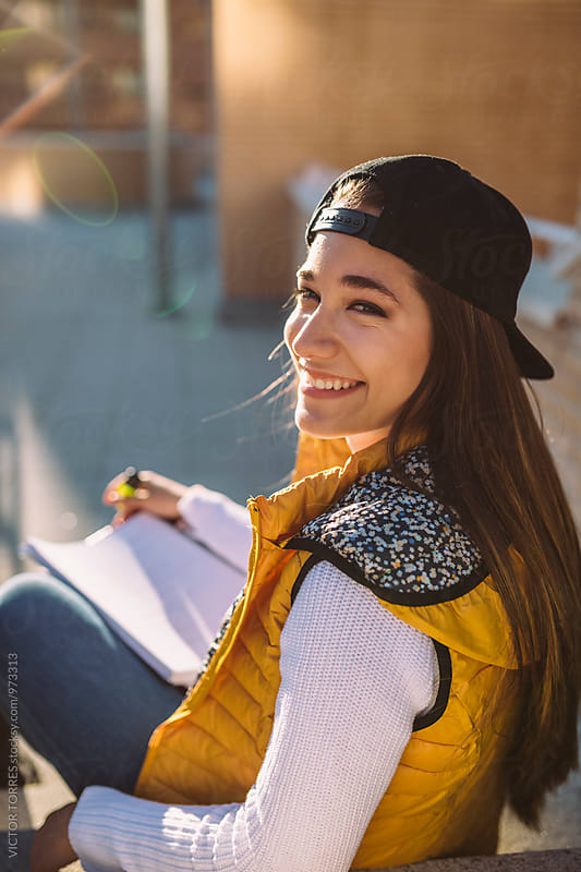 Pretty Teenager Doing Homework in the Street by VICTOR TORRES for Stocksy United