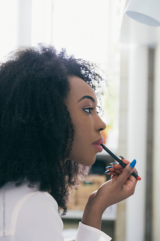 Young black woman putting putting makeup in front of the mirror by Lior + Lone for Stocksy United