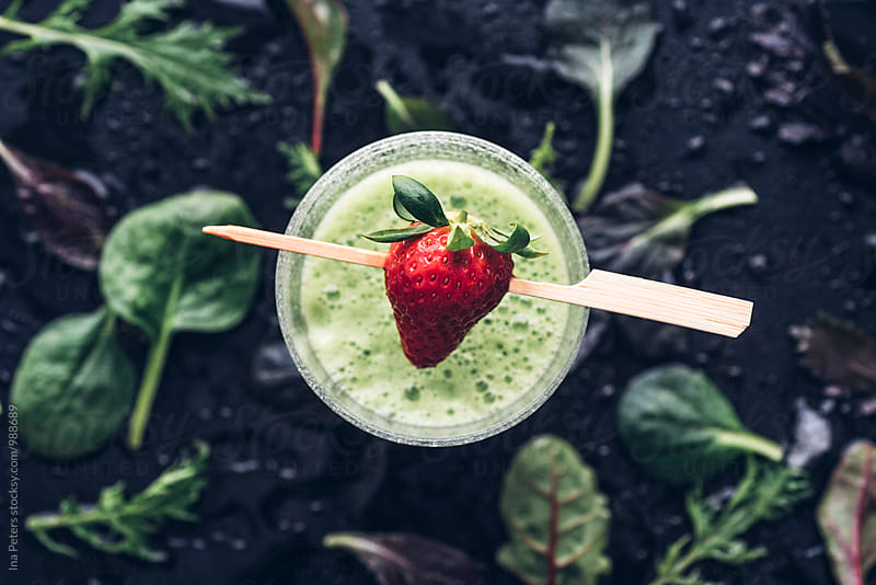Food: Green Smoothie with strawberry, wild herbs salad, apple juice and banana by Ina Peters for Stocksy United