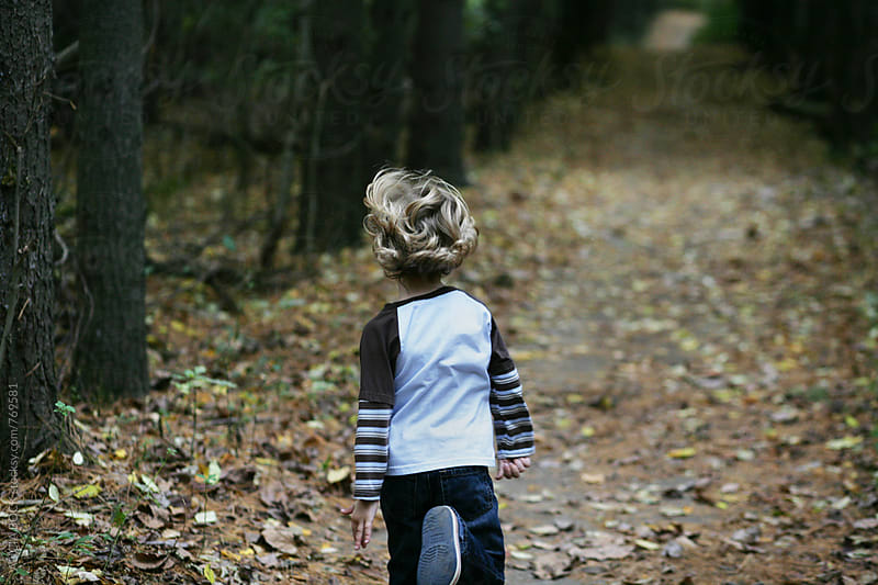 A Curly Haired Boy Running Through An Autumn Forest by ALICIA BOCK for Stocksy United