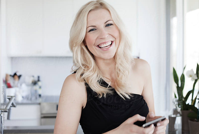 Very happy smiling woman with smart phone in her kitchen. by W2 Photography for Stocksy United