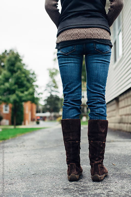 Woman in jeans and boots standing on a sidewalk by Gabriel (Gabi) Bucataru for Stocksy United