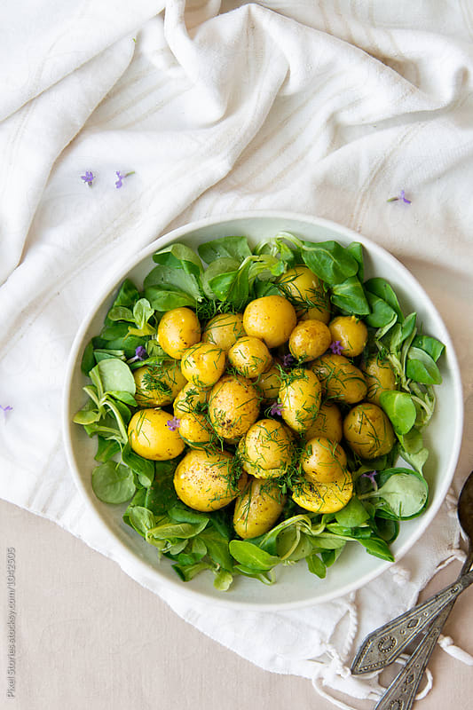 Potato salad with curry sauce and baby spinach by Pixel Stories for Stocksy United