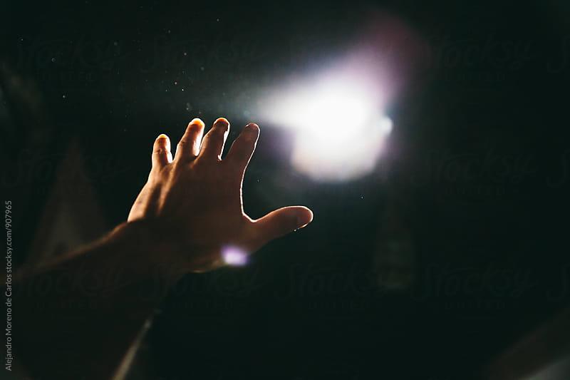 Hand reaching light by Alejandro Moreno de Carlos for Stocksy United
