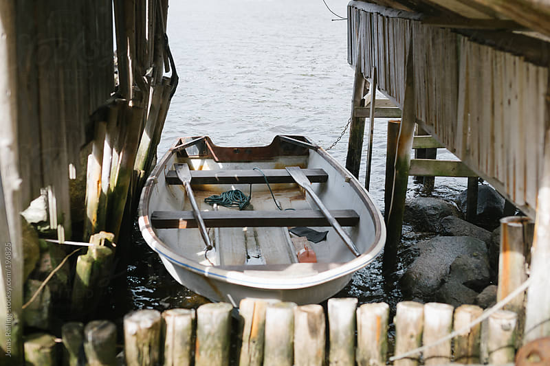Boat house with a white rowing boat by Jonas Räfling for Stocksy United
