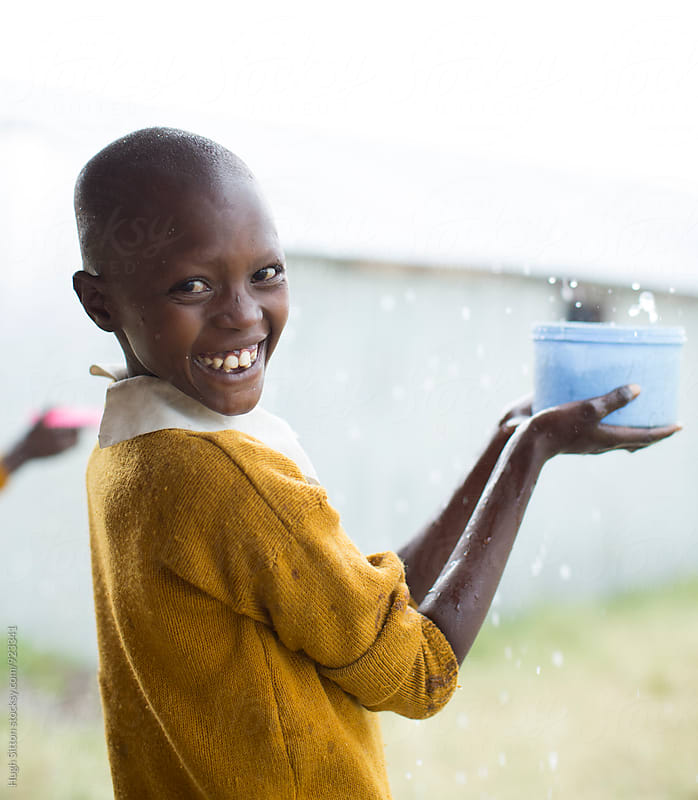 School girl having fun in the rain. Kenya. by Hugh Sitton for Stocksy United