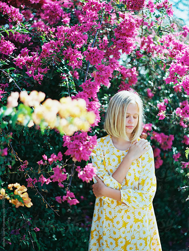 girl in yellow floral dress in front of pink and yellow flowers by wendy laurel for Stocksy United