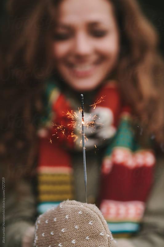 Detail shot of beautiful woman holding sparkler by Aleksandar Novoselski for Stocksy United