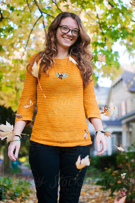 A young woman standing while leaves fall from a tree by Chelsea Victoria for Stocksy United