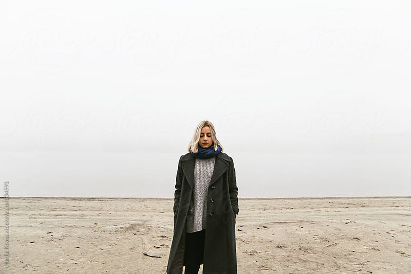 Young woman standing on the beach during the fog - horizontal by Marija Kovac for Stocksy United