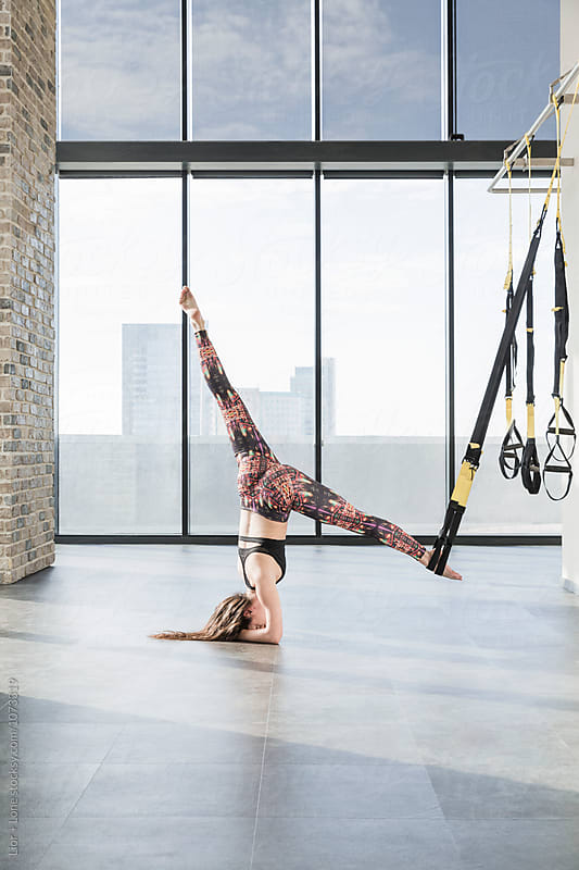Young female athlete doing shoulder stand with straps in studio by Lior + Lone for Stocksy United
