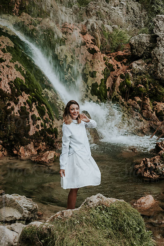 Beautiful young woman by the waterfall by Natasa Kukic for Stocksy United
