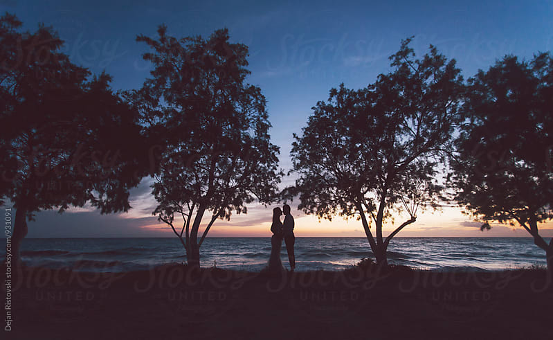 Couple standing on a sunset. by Dejan Ristovski for Stocksy United