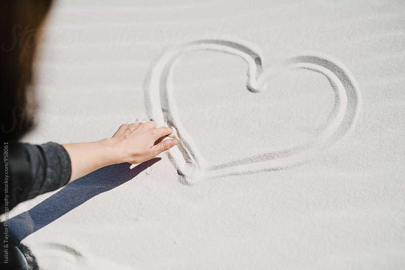 Woman drawing a heart in the sand by Isaiah & Taylor Photography for Stocksy United