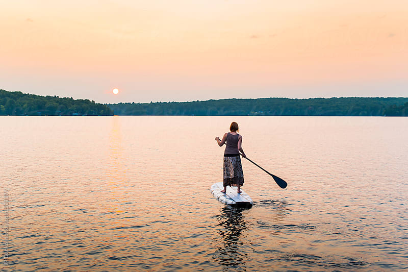 Woman Paddling Into Sunset on Stand Up Paddle Board by JP Danko for Stocksy United