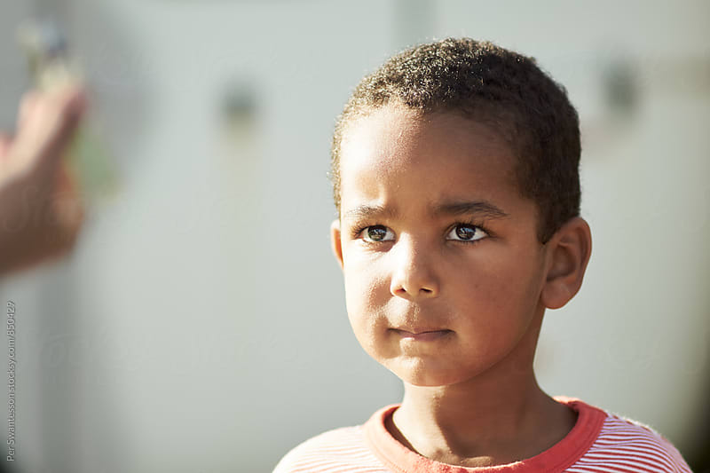 Cute serious boy listening to parent by Per Swantesson for Stocksy United