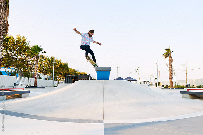 Professional skater doing trick in skate park by Guille Faingold for Stocksy United