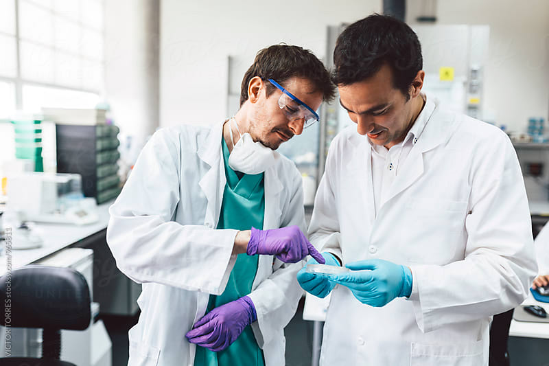 Biologists Checking Tests in a Professional Laboratory by Victor Torres for Stocksy United