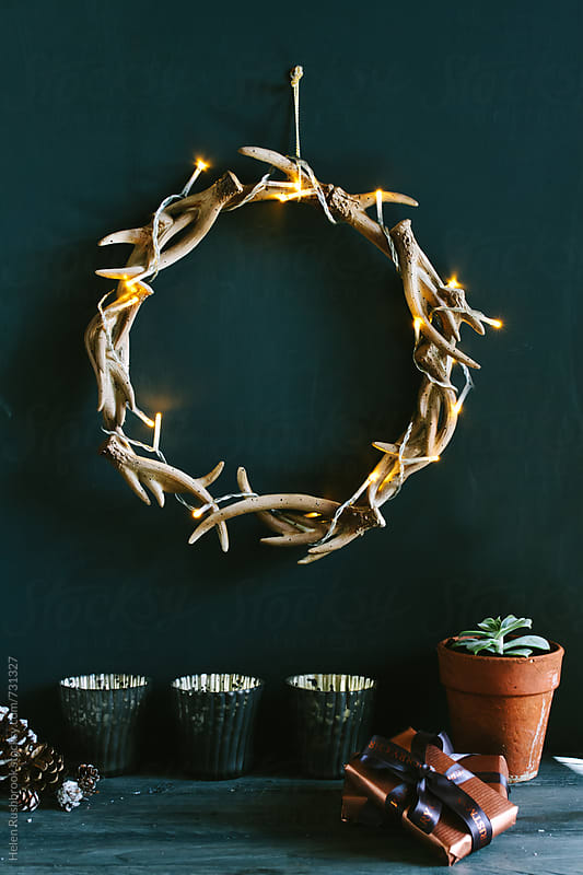 A lit antler wreath and copper-themed Christmas gifts. by Helen Rushbrook for Stocksy United