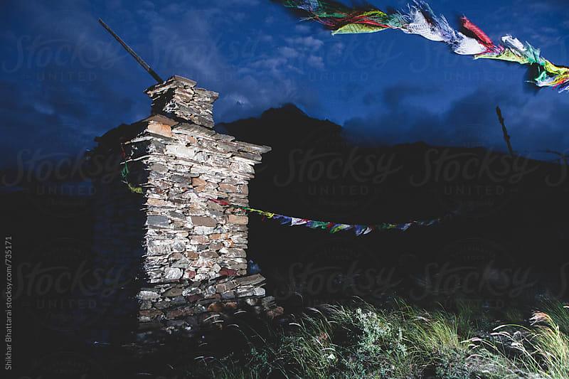 A chorten atop a hill light up at twilight. by Shikhar Bhattarai for Stocksy United