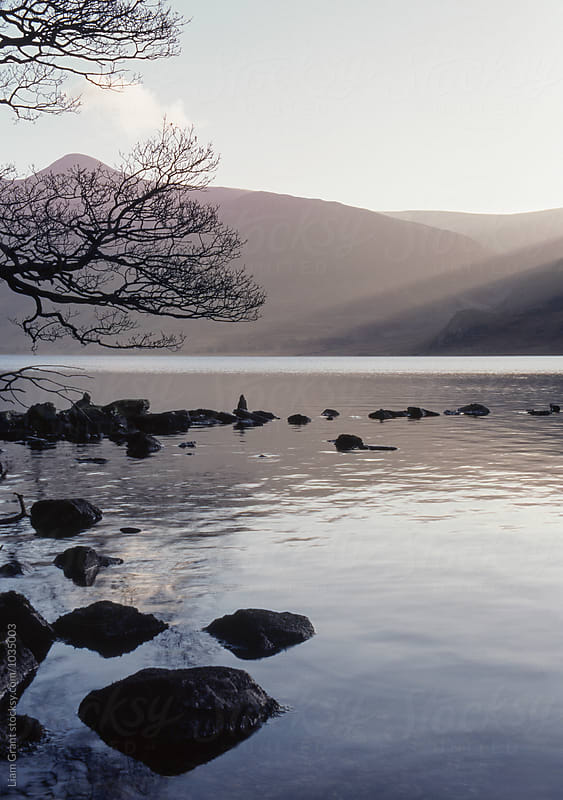 Shafts of sunlight at sunset of Crummock Water. Cumbria, UK. by Liam Grant for Stocksy United