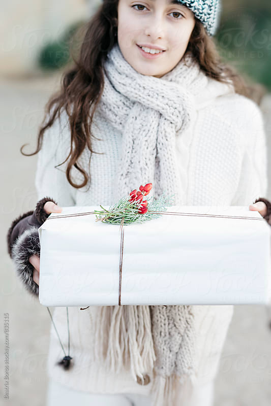 Preteenager girl holding a Christmas gift box and looking at camera by Beatrix Boros for Stocksy United