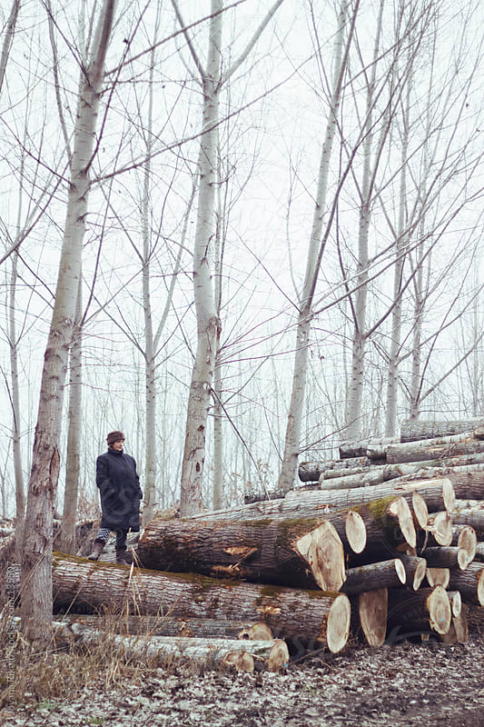 Mature woman standing on a woodpiles in the forest by Jovana Rikalo for Stocksy United
