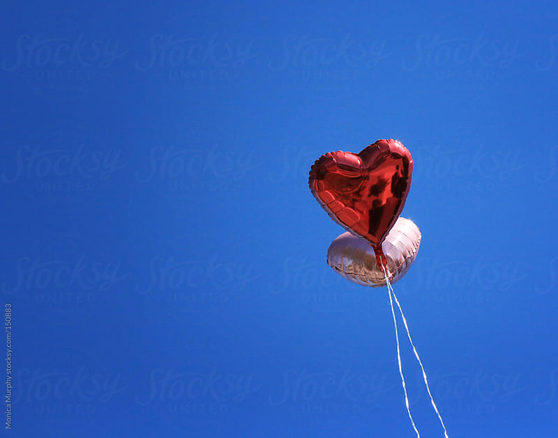 Heart balloons floating up in the sky by Monica Murphy for Stocksy United