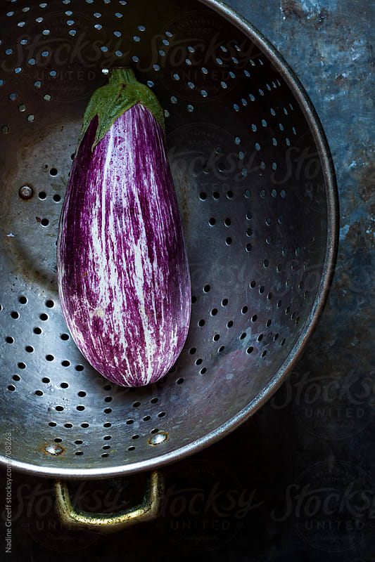 Purple eggplant in colander by Nadine Greeff for Stocksy United
