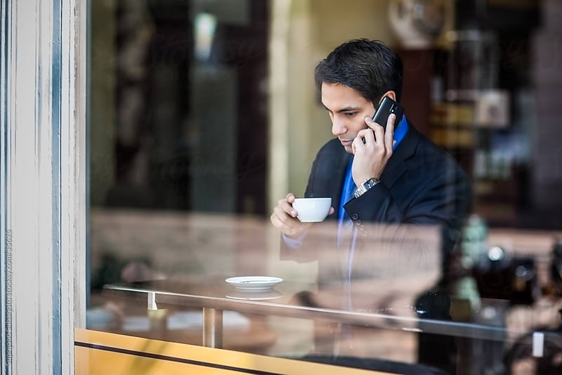 Indian businessman listening to the phone while drinking coffee in a cafe by Suprijono Suharjoto for Stocksy United